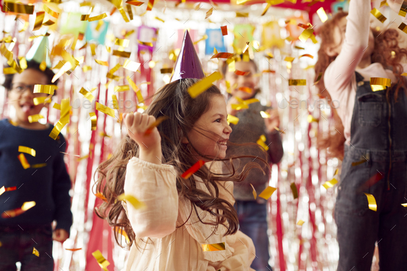 Group Of Children In Party Hats Celebrating At Birthday Party With Streamers And Gold Confetti - Stock Photo - Images