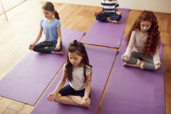 Group Of Children Sitting On Exercise Mats And Meditating In Yoga Studio - Stock Photo - Images