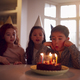 Boy Blowing Out Candles On Cake As He Celebrates Birthday With Group Of Friends At Home - PhotoDune Item for Sale