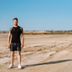 Confident young sportsman standing at beach - PhotoDune Item for Sale