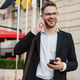 Handsome joyful businessman using wireless earphone and mobile phone - PhotoDune Item for Sale