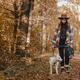 Stylish woman with backpack hiking with white dog in sunny autumn woods. Cute swiss shepherd puppy - PhotoDune Item for Sale