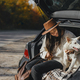 Stylish woman sitting with white dog in car trunk at sunny autumn trees. Road trip with pet - PhotoDune Item for Sale