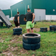 Participants in an obstacle course dragging wheels - PhotoDune Item for Sale
