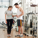 Personal trainer measuring a woman waist at the fitness club - PhotoDune Item for Sale