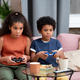 Cute boy and girl of African ethnicity playing video game on couch at home - PhotoDune Item for Sale