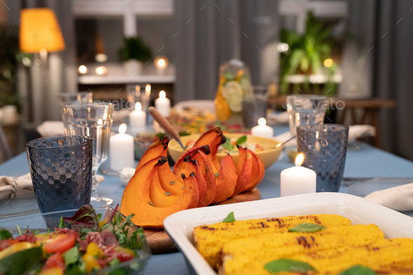 Part of served festive table with wineglasses, burning candles, homemade food - Stock Photo - Images