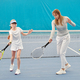 Young female tennis trainer in activewear showing teenage girl how to use racket - PhotoDune Item for Sale
