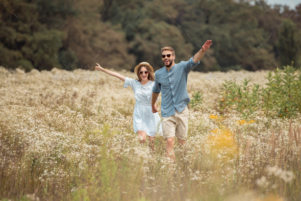 happy lovers holding hands while running in field with wild flowers - Stock Photo - Images