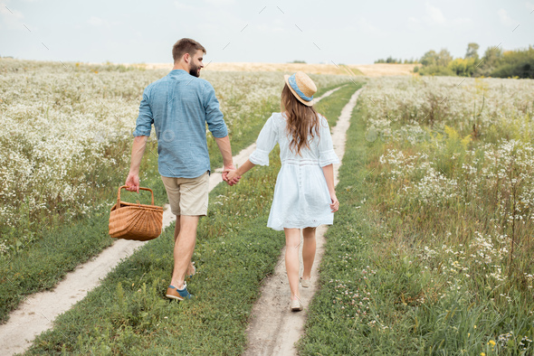 rear view of couple with picnic basket holding hands while walking in field - Stock Photo - Images