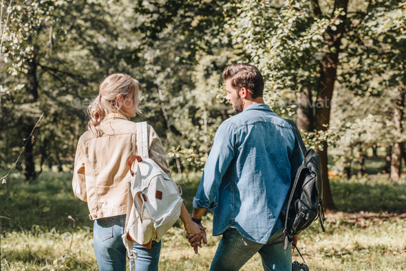 back view of romantic couple holding hands in park - Stock Photo - Images