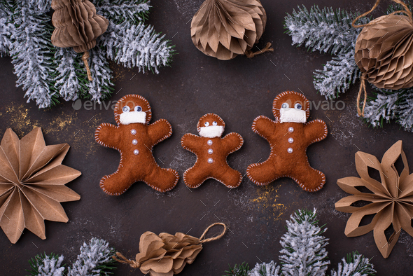 Gingerbread man from felt in face mask - Stock Photo - Images
