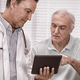 Doctor and senior patient using digital tablet - PhotoDune Item for Sale