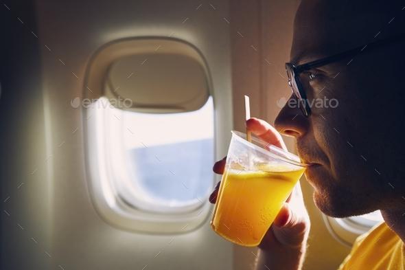 Young passenger enjoying dring during flight - Stock Photo - Images