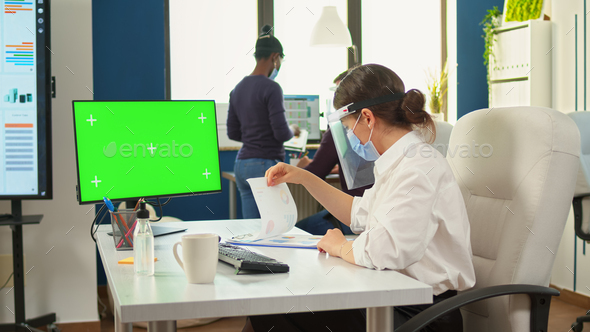Manager with face mask typing on computer with green screen - Stock Photo - Images