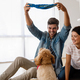 Cheerful young loving couple is playing with their dog at home - PhotoDune Item for Sale