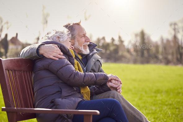Loving Senior Couple Sitting On Seat Enjoying Autumn Or Winter Walk Through Park Together - Stock Photo - Images