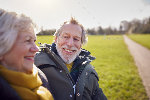 Loving Senior Couple Sitting On Seat Enjoying Autumn Or Winter Walk Through Park Together - Stock Photo - Images