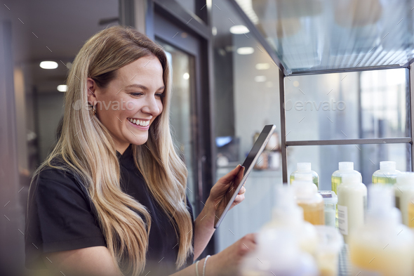 Female Stylist Or Business Owner In Hairdressing Salon Using Digital Tablet To Check Beauty Products - Stock Photo - Images