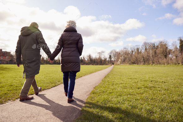 Rear View Of Loving Senior Couple Holding Hands Enjoying Autumn Or Winter Walk Through Park Together - Stock Photo - Images