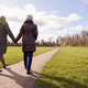Rear View Of Loving Senior Couple Holding Hands Enjoying Autumn Or Winter Walk Through Park Together - PhotoDune Item for Sale