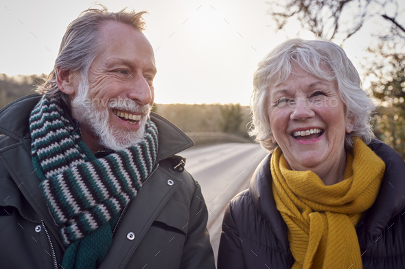 Portrait Of Loving Senior Couple Enjoying Autumn Or Winter Walk Along Country Road Together - Stock Photo - Images