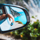Female hand mirrored in the car side view mirror. Blue mediterranean sea and white rocks in - PhotoDune Item for Sale