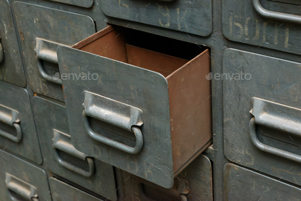 Old gray metal cabinet with drawers, one drawer opened - Stock Photo - Images