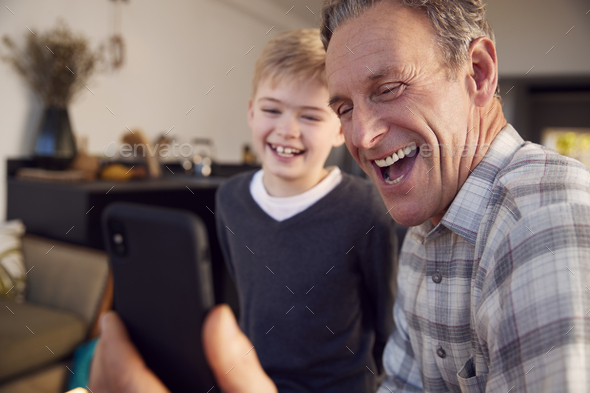 Grandson With Grandfather Smiling And Taking Selfie On Mobile Phone At Home - Stock Photo - Images