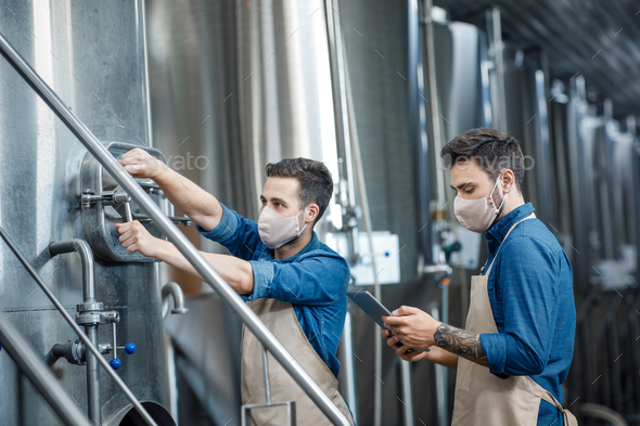 Workers at brewery and fermentation of beer to produce beverage - Stock Photo - Images