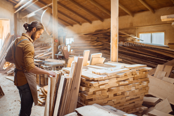 Carpenter at the wood storage - Stock Photo - Images