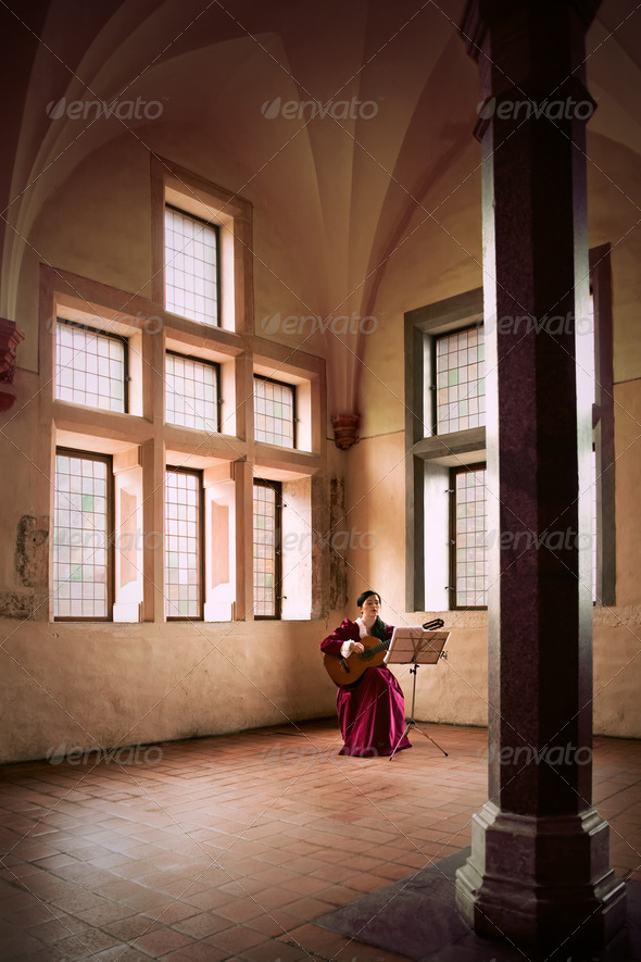 Woman playing guitar in Malbork Castle. - Stock Photo - Images