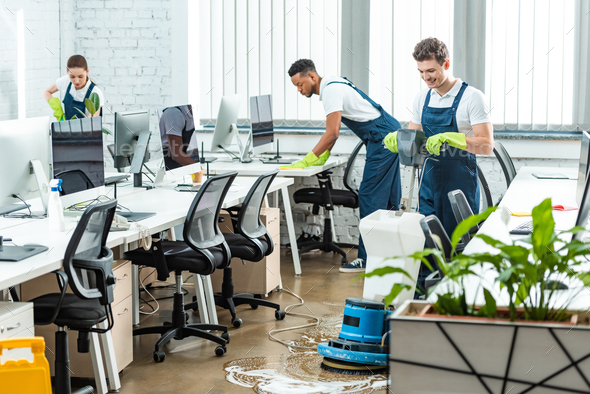 multicultural team of cleaners working in modern open space office - Stock Photo - Images