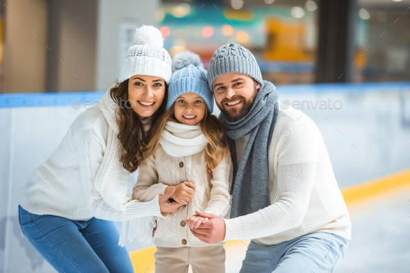 portrait of cheerful parents and daughter in sweaters looking at camera on skating rink - Stock Photo - Images