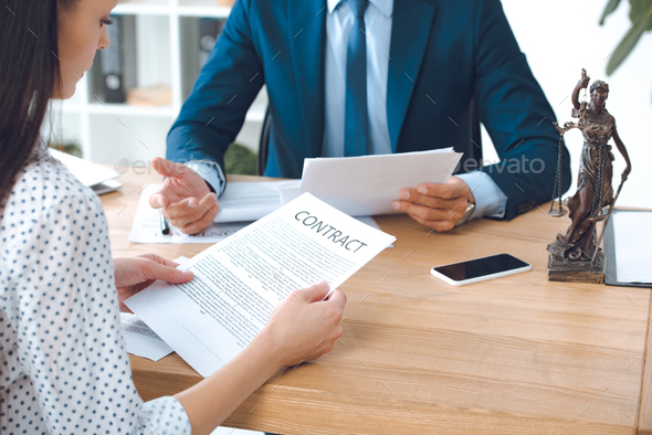 cropped shot of lawyer holding papers and client reading contract in office - Stock Photo - Images