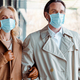Panoramic shot of business couple in medical masks looking away near building on urban street - PhotoDune Item for Sale