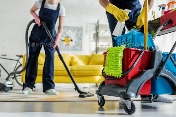 cropped view of cleaner in rubber gloves holding spray bottle near cleaning trolley and coworker - Stock Photo - Images