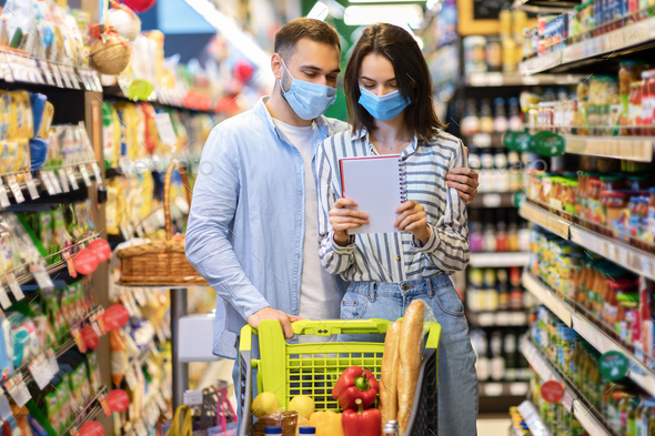Couple Wearing Face Masks In Hypermarket, Checking Shopping List - Stock Photo - Images