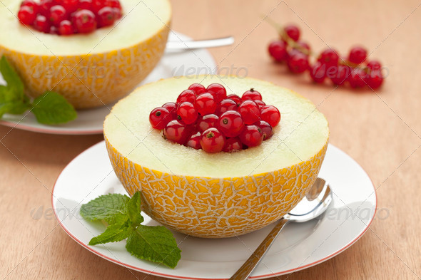 Melon filled with red currants - Stock Photo - Images