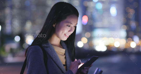Woman looks at mobile phone in city at night - Stock Photo - Images