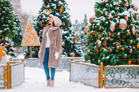Happy girl near fir-tree branch in snow for new year - Stock Photo - Images