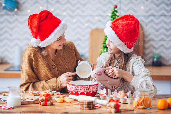 Little girls making Christmas gingerbread house at fireplace in decorated living room - Stock Photo - Images