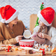 Little girls making Christmas gingerbread house at fireplace in decorated living room - PhotoDune Item for Sale