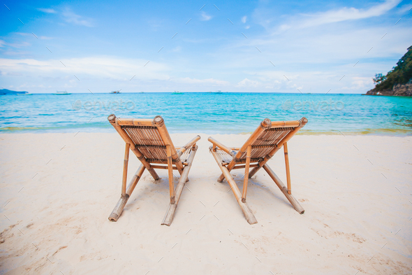 White lounge chairs on a beautiful tropical beach - Stock Photo - Images