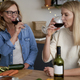 Two women drinking red wine in the kitchen during Christmas - PhotoDune Item for Sale