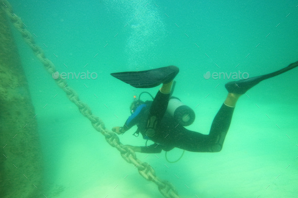Male scuba diver with equipment diver swims in water - Stock Photo - Images
