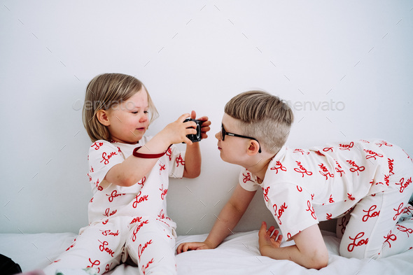 Two children in matching outfits playing with camera. - Stock Photo - Images