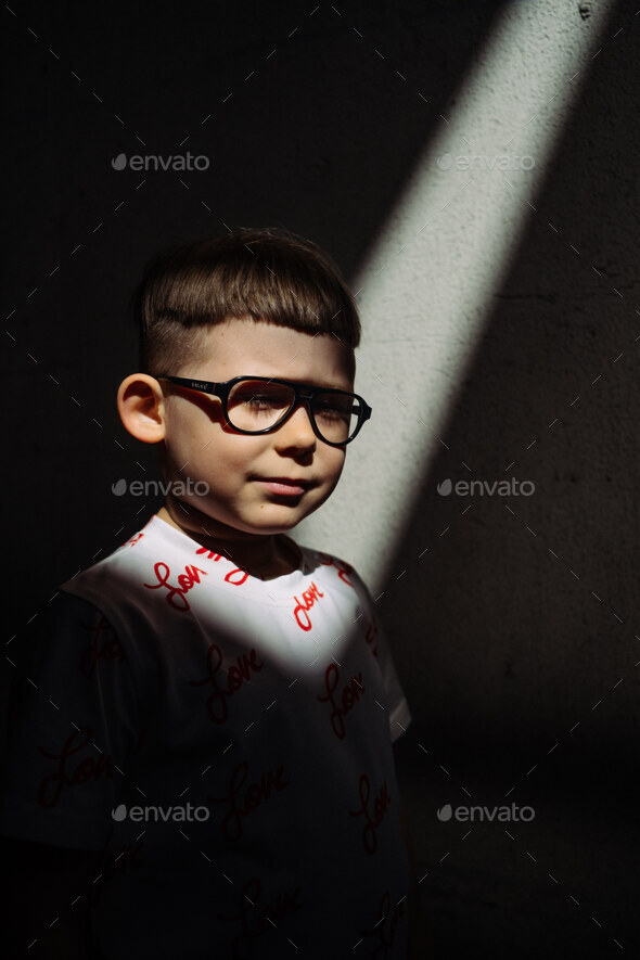 Boy in shaft of light, urban. - Stock Photo - Images