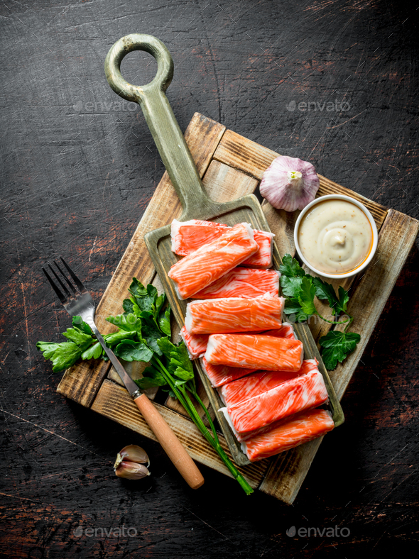 Crab sticks on wooden tray with herbs, garlic and sauce. - Stock Photo - Images