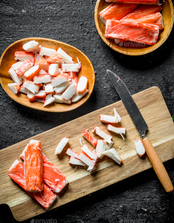 Sliced crab sticks on a cutting Board with a knife. - Stock Photo - Images